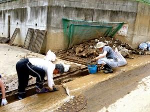 Volunteers at work clearing drains of rocks.